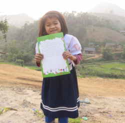 Thuy smiling brightly with the letter she wrote to her sponsor