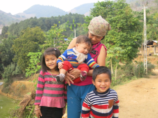 Thuy (left) with her mom holding her younger brother (center), and her cousin (right)