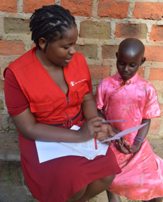 Community Sponsorship Officer Eva helping Hajara read her first sponsor letter
